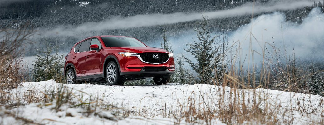 2019 Mazda CX-5 exterior shot with red paint color parked on a snow hill with fog and mist covering a forest mountain behind it