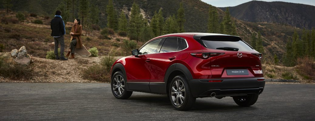 2020 Mazda CX-30 compact crossover SUV exterior side rear shot with soul red crystal paint color parked in a mountain wilderness as a couple waits outside