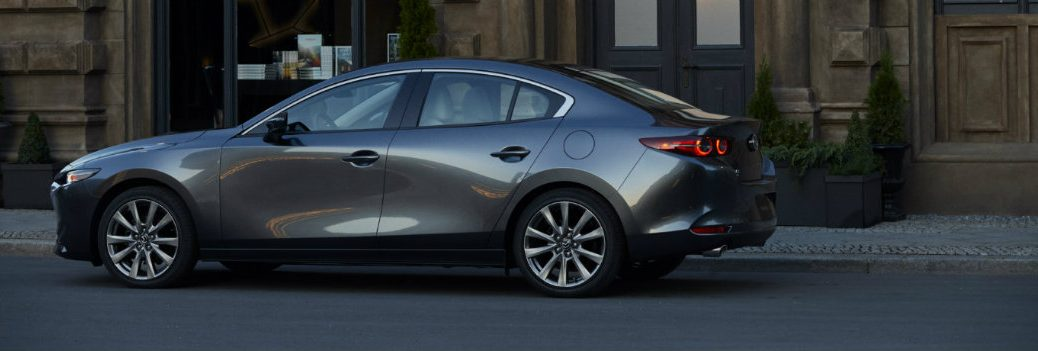2019 Mazda3 sedan exterior side shot with gray metallic paint color parked outside a brown stone building in the city
