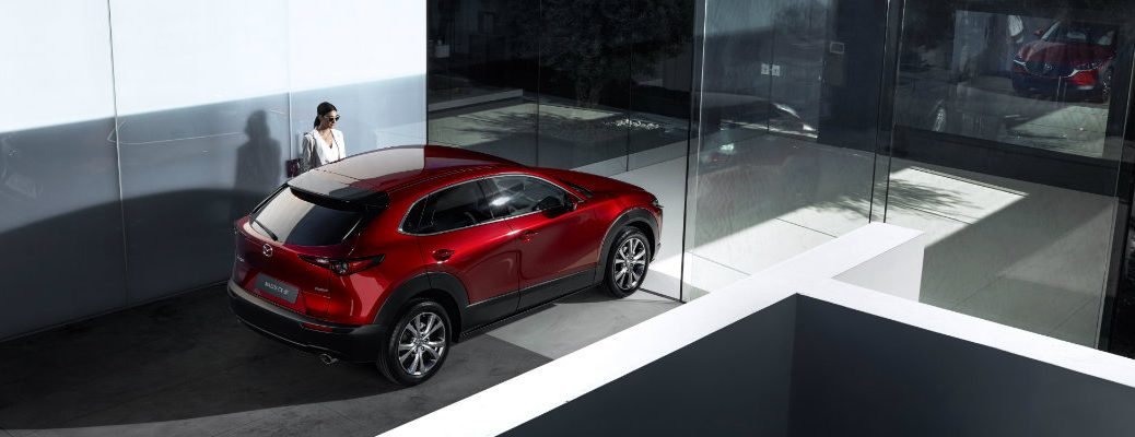 2020 Mazda CX-30 compact crossover SUV overhead rear shot with soul red crystal paint color parked in a fancy glass building as a women enters the driver's door