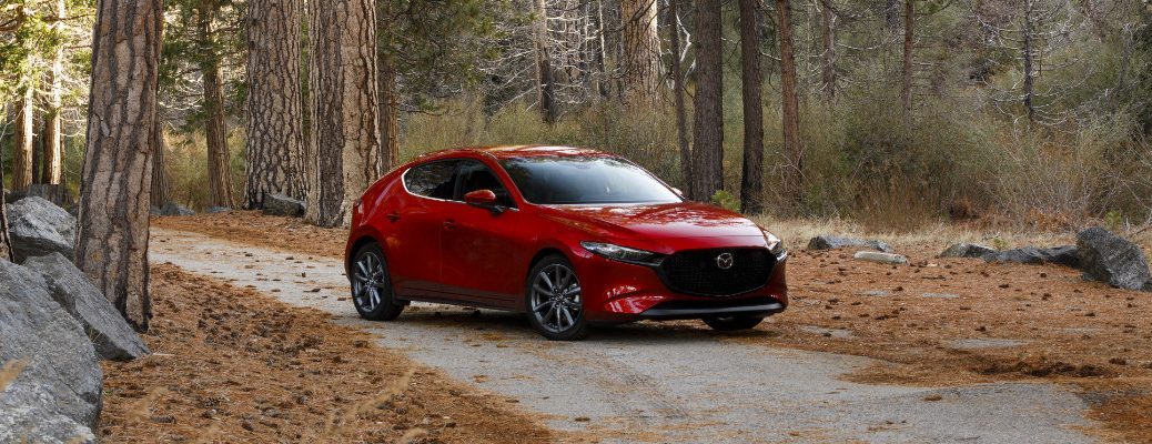 2019 Mazda3 hatchback exterior shot with soul red crystal paint color parked in an open forest path