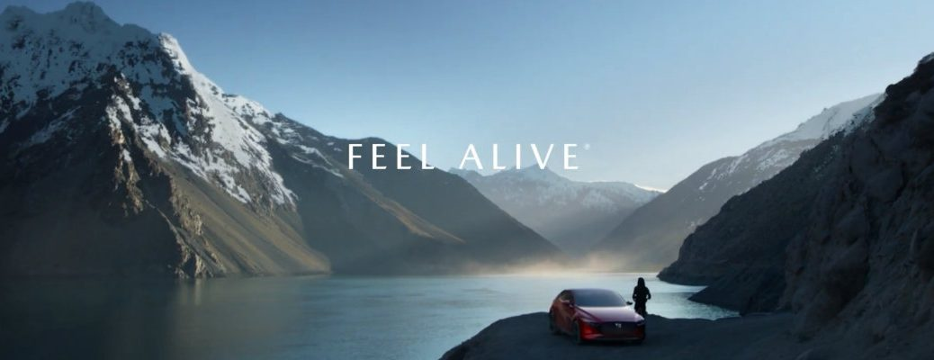 Mazda Feel Alive Commercial Marketing Campaing Banner with a woman with her 2019 Mazda3 hatchback parked near a snowcapped mountain and icy lake