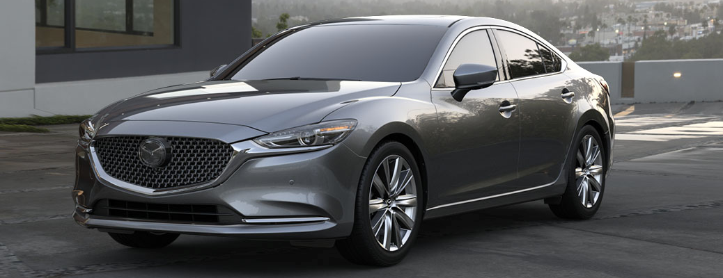 2019 Mazda6 exterior shot with machine gray metallic paint color parked outside a luxury house in California within a foggy sky