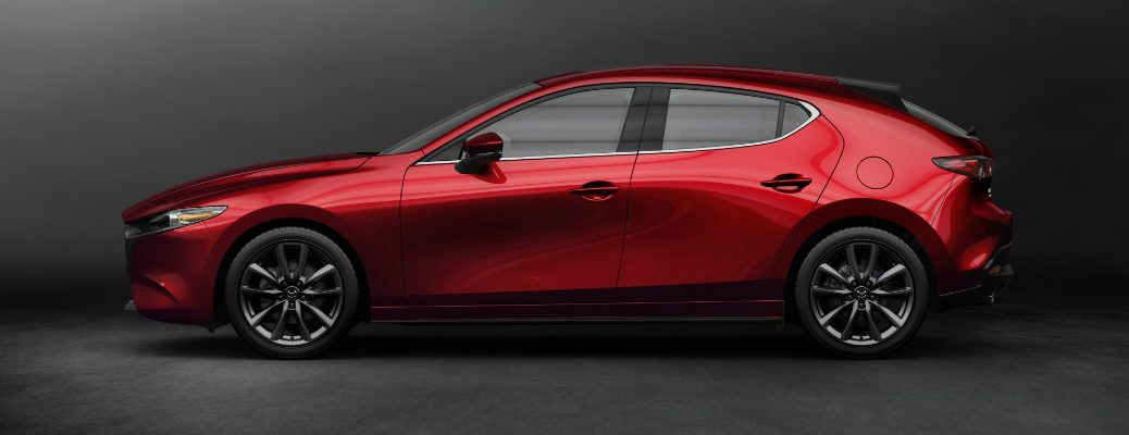 2019 Mazda3 Hatchback exterior side shot with red paint color parked in an empty showroom