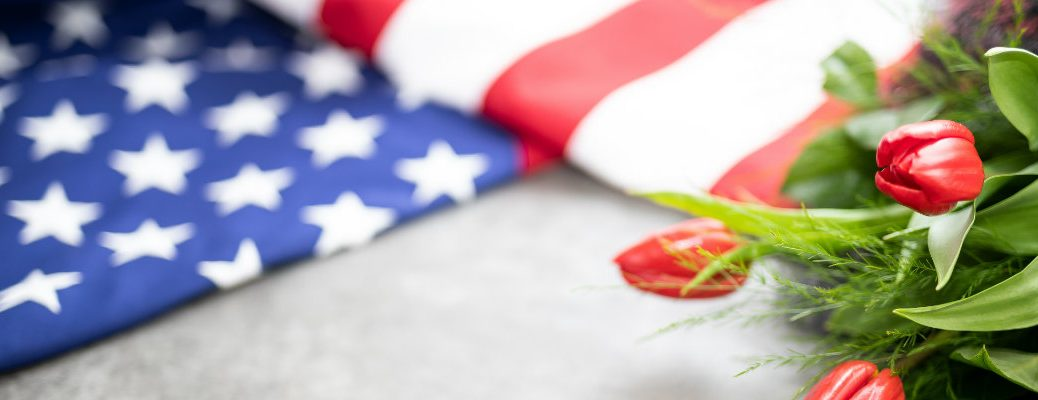 a folded American flag on the ground next to a bushel of red tulips for Memorial Day