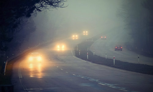 Foggy Highway Road with Cars with Headlights on