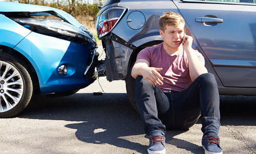 Man sitting by Car Calling Phone after a Car Accident