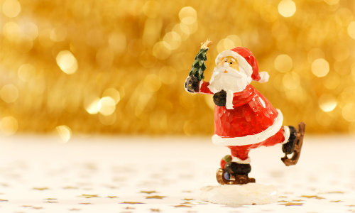 Tiny ornamental Santa on a tabletop with a gold background