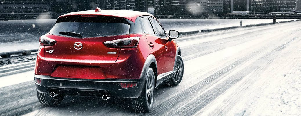2018 Mazda CX-3 driving outside a city in snow