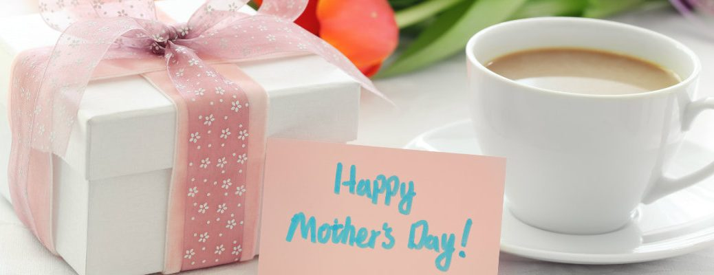 happy mother's day card next to a cup of coffee, a bouquet of lowers, and a wrapped gift