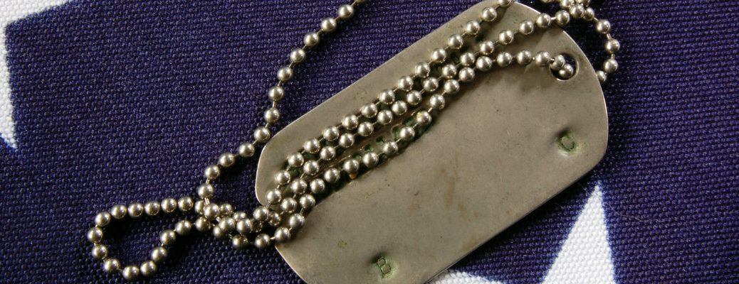 Metal dog tag laying atop an American flag memorial day ceremony