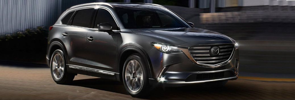 2019 and 2018 Mazda CX-9 design exterior shot driving at night with LED lights on near stone brick steps