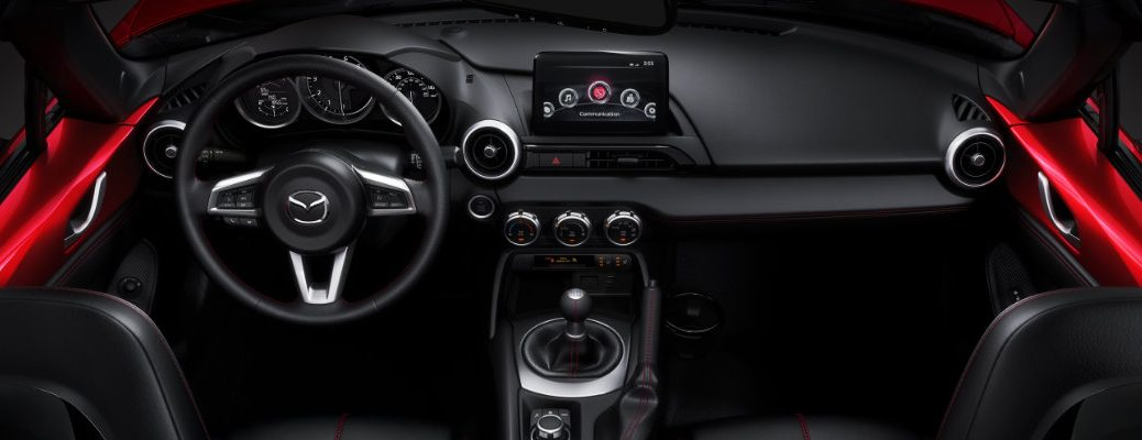 2018 Mazda MX-5 Miata interior with top down showing the seating upholstery and colors, steering wheel and badge, and dashboard tech and driver's display