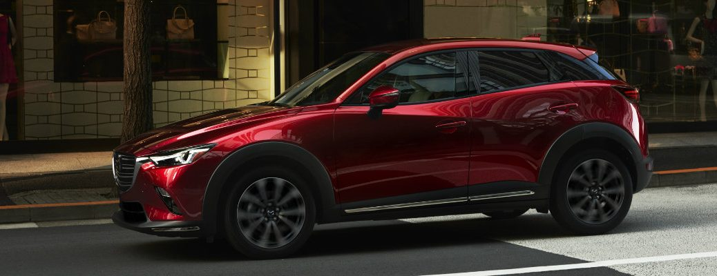 2019 Mazda CX-3 exterior side shot with red paint color parked next to a fashion store on a city street