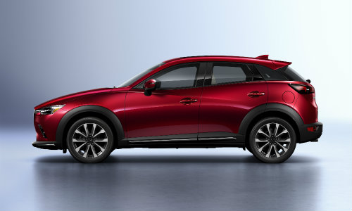 2019 Mazda CX-3 exterior side shot with red paint color parked in a blank white showcase room