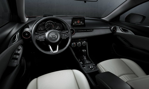2019 Mazda CX-3 interior shot of front seating upholstery, dashboard layout design, and steering wheel configuration