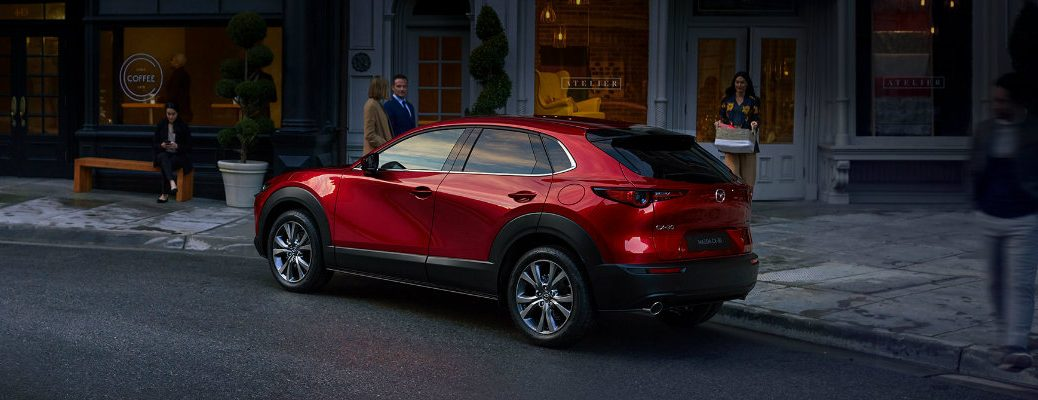 2020 Mazda CX-30 compact crossover SUV exterior side shot with soul red crystal paint color parked outside a fancy cafe as people walk by