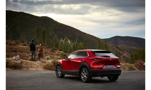 2020 Mazda CX-30 compact crossover SUV exterior side rear shot with soul red crystal paint color parked in a mountain wilderness as a couple waits outside small