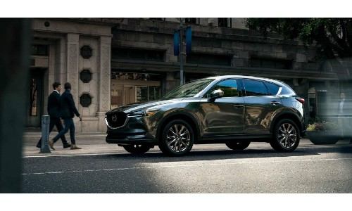 2019 Mazda CX-5 signature trim exterior side shot with metallic gray paint color parked near a cafe as people walk by
