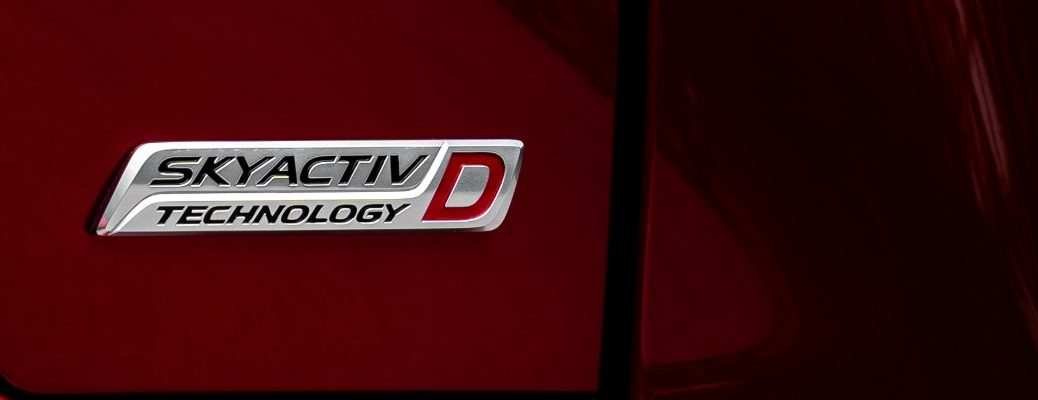 SKYACTIV-D Technology badge on the back of a 2019 Mazda CX-5 Signature SKYACTIV-D model with a red crystal paint color