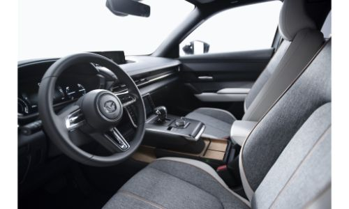 Mazda MX-30 electric vehicle EV at 2019 Tokyo Motor Show debut interior side view of front seating upholstery, steering wheel, transmission, and dashboard design