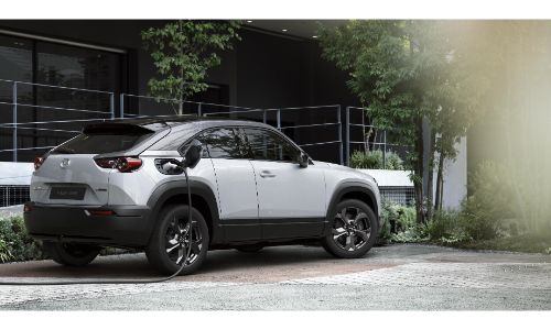 Mazda MX-30 electric vehicle EV at 2019 Tokyo Motor Show debut parked outside a building near trees as its plugged into a charging station