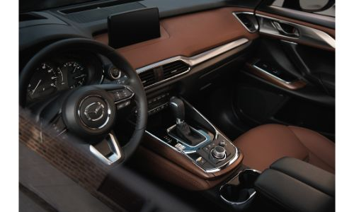 2020 Mazda CX-9 SUV interior shot through driver's side window showing seating upholstery and steering wheel and dashboard design and trimming