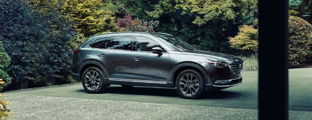 2020 Mazda CX-9 exterior side shot with Machine Gray Metallic paint color parked outside a luxury forest home surrounded by colorful bushes and trees