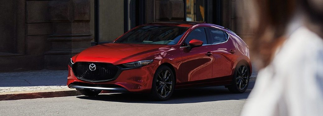 A red 2020 Mazda3 Hatchback parked at a traffic sign in the middle of an urban area.