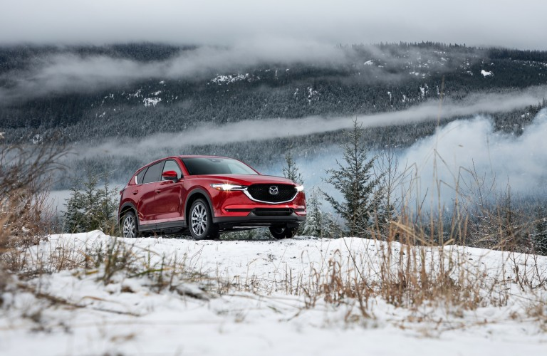 A red 2020 Mazda CX-5 driving over a snowy hill.