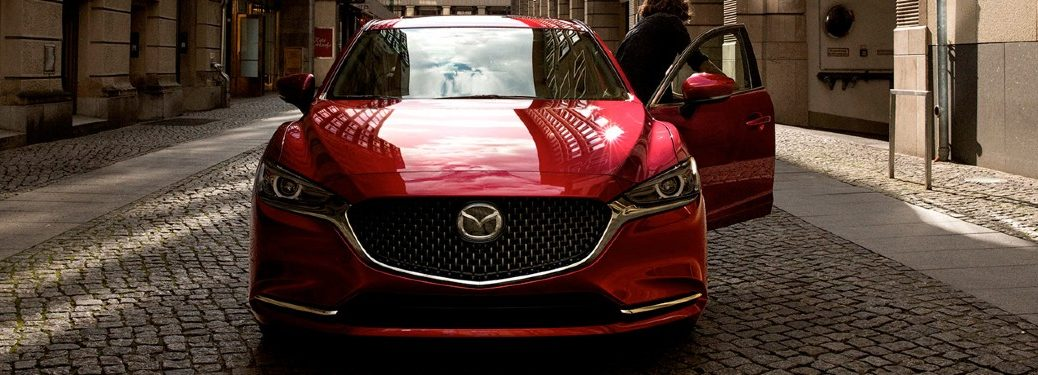 A red 2020 Mazda6 parked on a cobblestone road with the driver getting out of the vehicle.