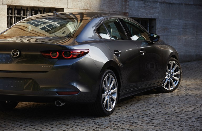 The rear and side view of a gray 2021 Mazda3 Sedan parked on a cobblestone street.