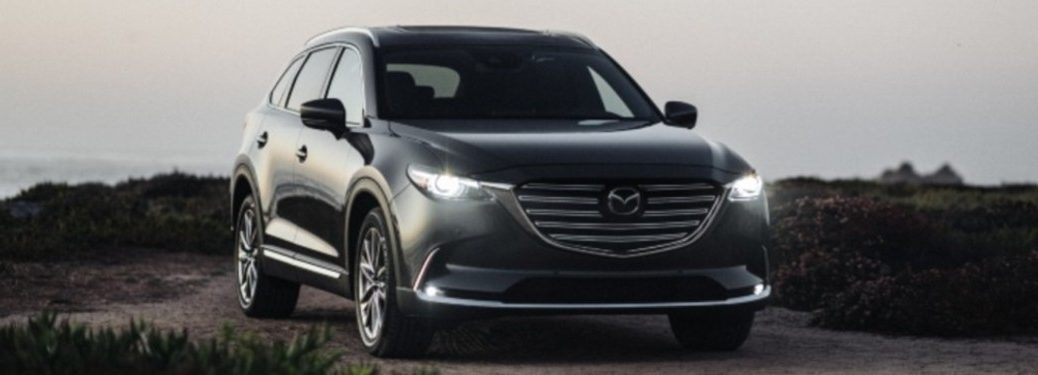 The exterior of a black 2020 Mazda CX-9 parked with its lights on.