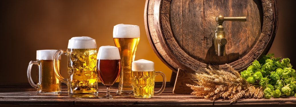 An image of several mugs of beer with an Oktoberfest beer barrel next to them.