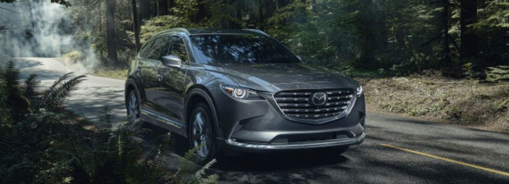 The front view of a gray 2021 Mazda CX-9 driving in a forested area.