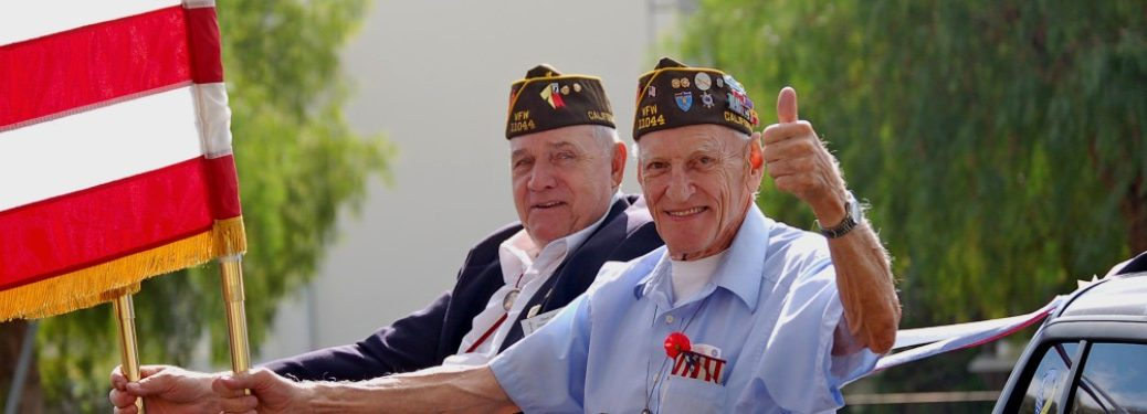 Two veterans smiling and holding an American flag during a rally.