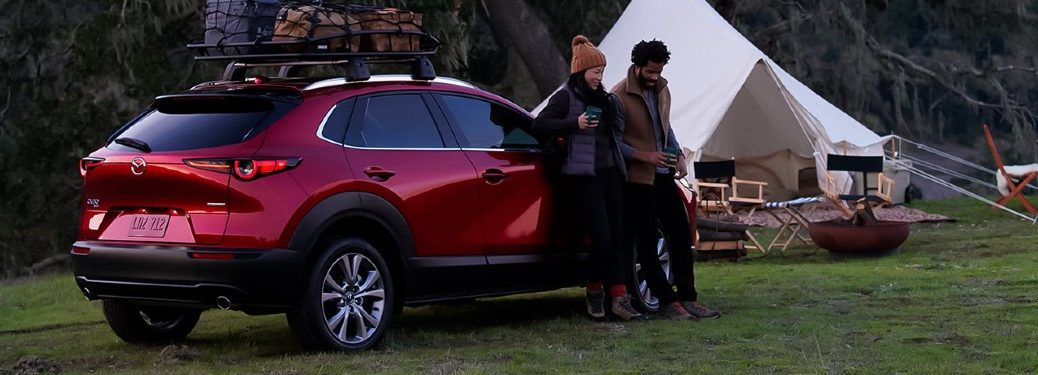 A couple sitting on a red 2021 Mazda CX-30 while out camping.