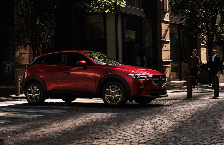 The side view of a 2021 Mazda CX-3 parked near a house.