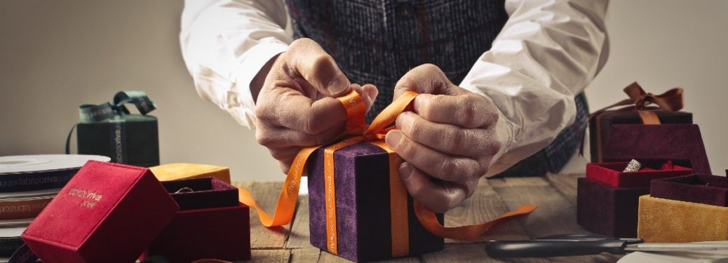 An older person wrapping a present with a bow on a table.