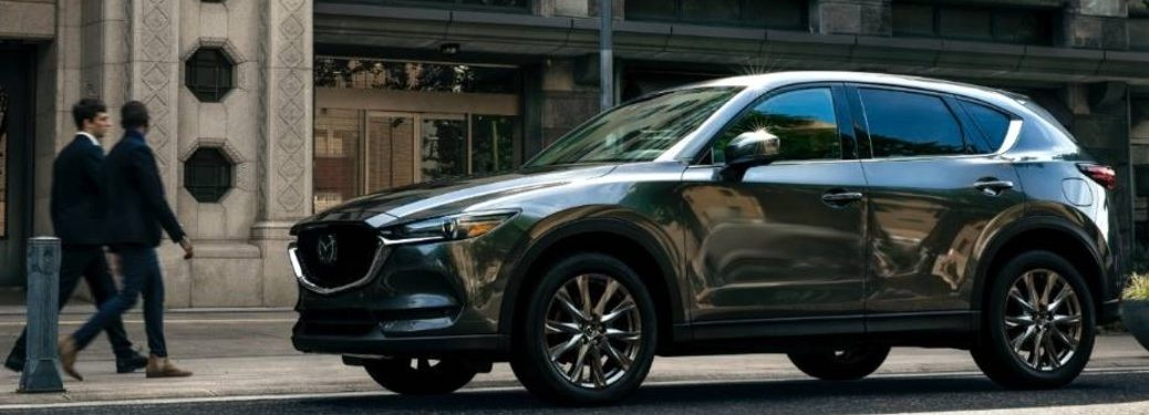 The side view of a gray 2021 Mazda CX-5 parked on the side of a city street.