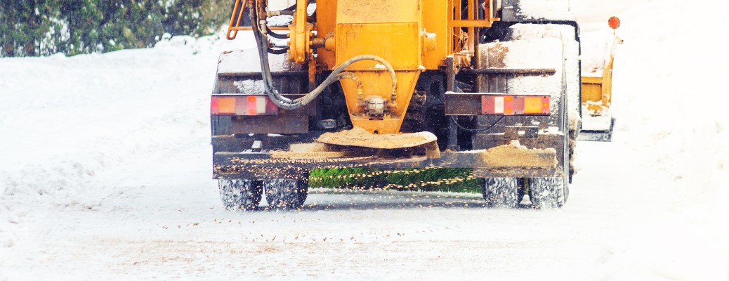 An orange municipal vehicle spreading salt and sand on a wintry road.