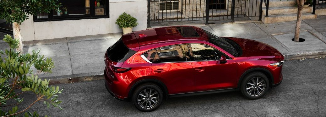 The top and side view of a red 2021 Mazda CX-5 parked on the side of a city street.