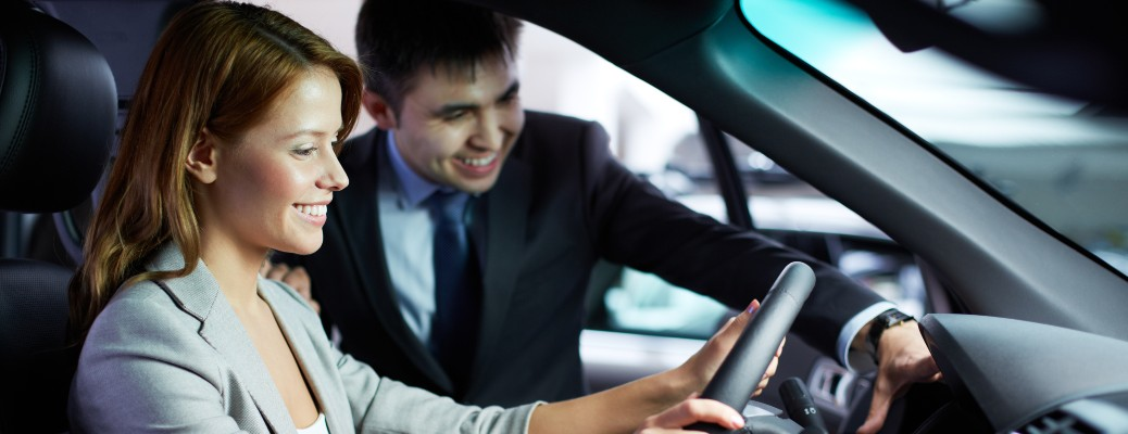 A woman sitting in a vehicle smiling next to a salesman.