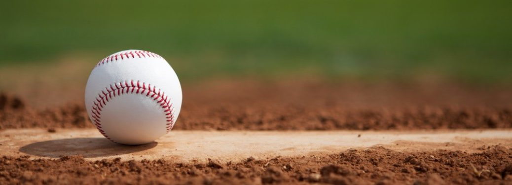 A baseball sitting on top of home plate on a baseball field.