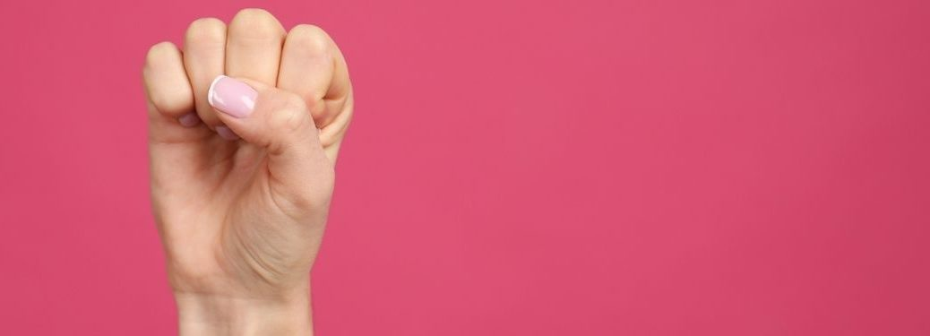Women showing fist as girl power symbol on pink background