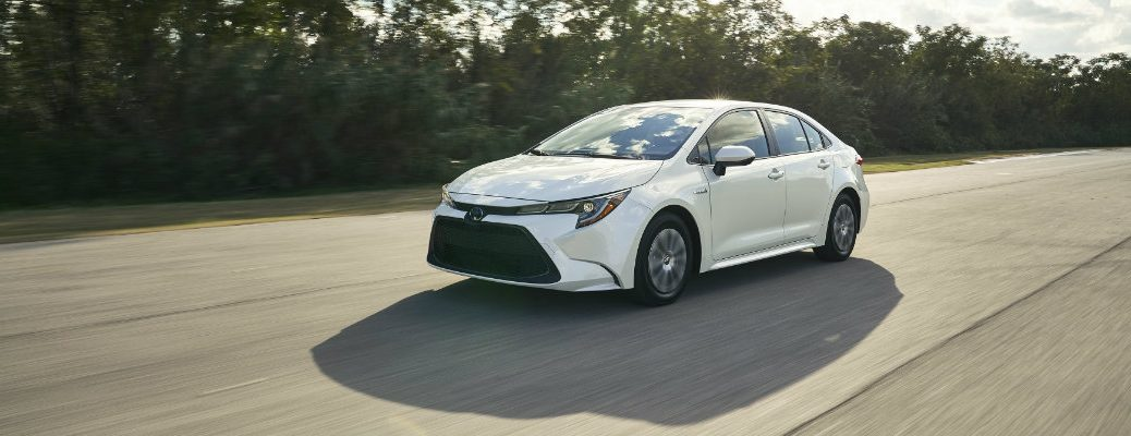White 2020 Toyota Corolla Hybrid driving on empty highway