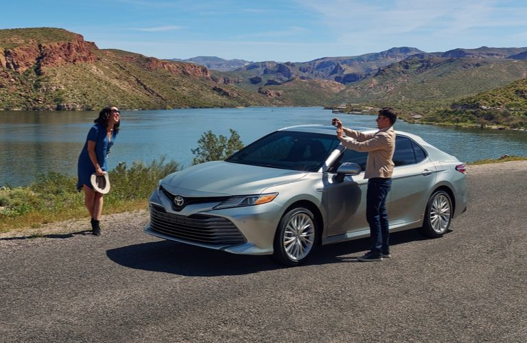 Exterior view of two people taking photos around a silver 2020 Toyota Camry Hybrid