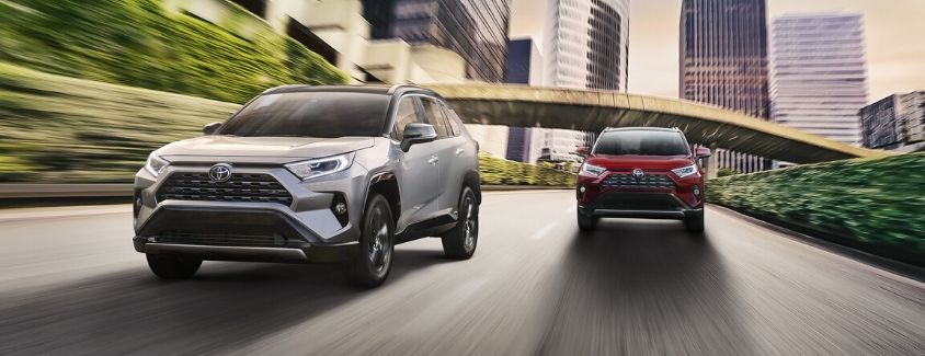 Exterior view of a silver 2020 Toyota RAV4 and a red 2020 Toyota RAV4 Hybrid driving down the road