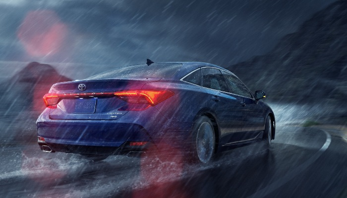2021 Toyota Avalon driving down a curved road in a storm