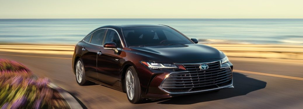 2021 Toyota Avalon driving down an oceanside road on a sunny day